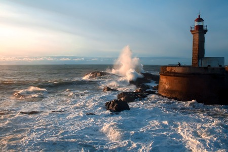 The waves of the Atlantic Ocean crash against the rocks at sunset by the lighthouse