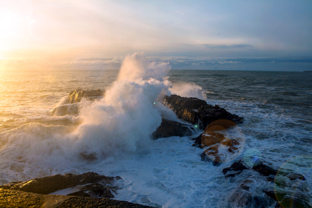 Waves of the Atlantic Ocean crashing against a rock at sunset. Imagens