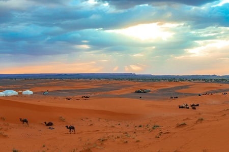 Sunrise in the western part of the Sahara Desert in Morocco. The suns rays break through the clouds and sanctify the campsite and camels at the foot of the desert.