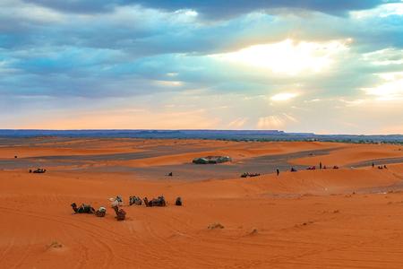 Wschód słońca w zachodniej części Sahary w Maroku. Promienie słoneczne przebijają się przez chmury i uświęcają obóz oraz wielbłądy u podnóża pustyni.