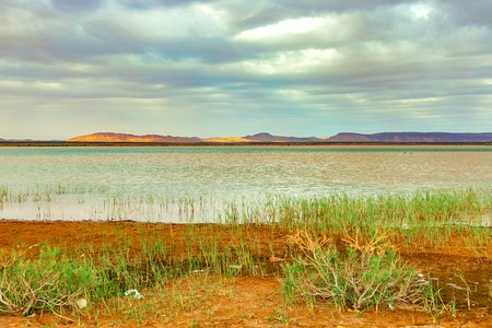 Lake in Morocco at dawn at the foot of the Sahara desert. The suns rays shine through the clouds. Banco de Imagens