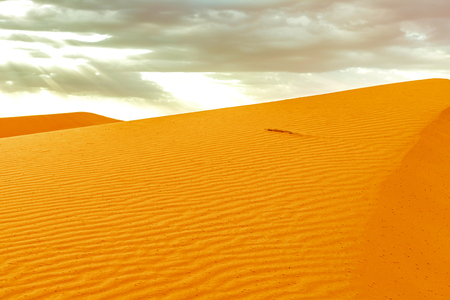 Beautiful sand dunes at sunrise in the Sahara Desert. The suns rays make their way through the clouds, Morocco 写真素材