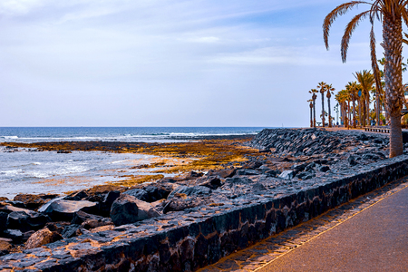 Small stones on a black beach, in the background are akean waves and a surfer. Tenerife Banque d'images