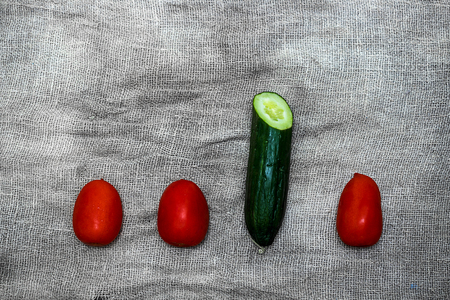 Vegetables on a gray background from flax. Tomato, yellow pepper, cucumber, lemon,radish