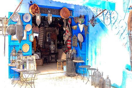 CHEFCHAOUEN, MOROCCO - APRIL 24, 2019: Colorful Moroccan fabrics and handmade souvenirs on the street in the blue city Chefchaouen, Morocco, Africa.