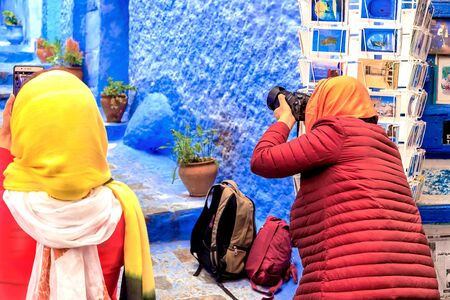Chefchaouen, Morocco - 24/04/2019: Tourists taking pictures in Chefchaouen, a beautiful city in northern Morocco visited by tourists from around the world.