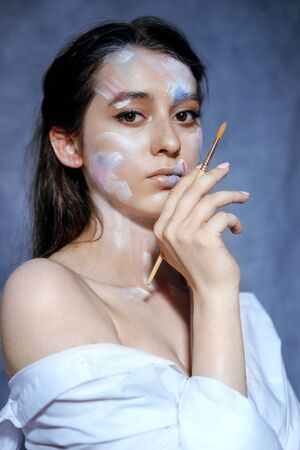 Creative fashion beauty portrait of a beautiful young woman with an artistic tassel in her hands. Model girl with professional make-up and body art on gray background. 写真素材