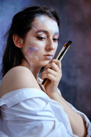 Creative fashion beauty portrait of a beautiful young woman with a brush for cosmetics. Model girl with professional makeup and body art on a gray background. 写真素材