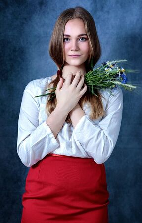 Dramatic portrait of a beautiful lonely girl with blond hair isolated on gray background in studio shot, Belarus Stockfoto