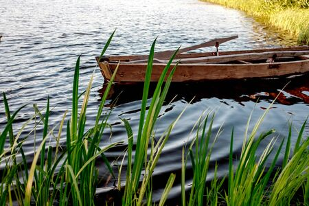 A small wooden rowing boat with a broken bottom on a calm lake near the shore. Belarus 写真素材 - 131970215