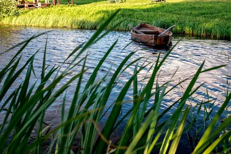 A small wooden rowing boat with a broken bottom on a calm lake near the shore. Belarus 写真素材 - 131971226