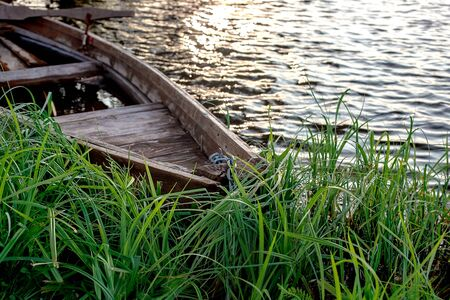 A small wooden rowing boat with a broken bottom on a calm lake near the shore. Belarus 写真素材 - 131970261