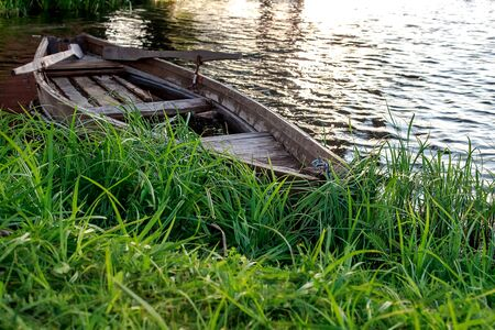 A small wooden rowing boat with a broken bottom on a calm lake near the shore. Belarus 写真素材 - 131970318
