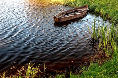 A small wooden rowing boat with a broken bottom on a calm lake near the shore. Belarus 写真素材 - 131970251