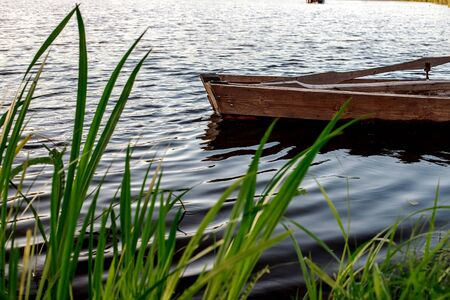 A small wooden rowing boat with a broken bottom on a calm lake near the shore. Belarus 写真素材 - 131971202