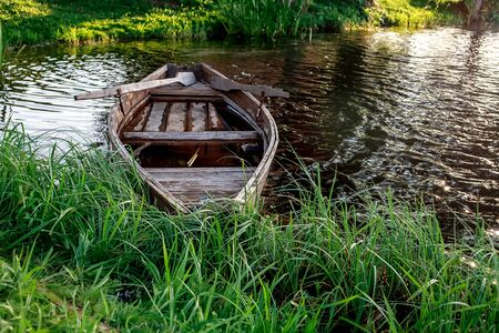 A small wooden rowing boat with a broken bottom on a calm lake near the shore. Belarus 写真素材 - 131970208