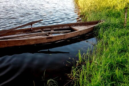 A small wooden rowing boat with a broken bottom on a calm lake near the shore. Belarus 写真素材 - 131970996
