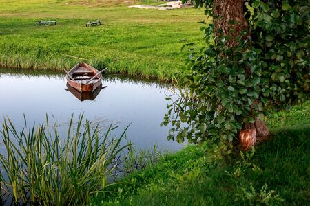 A small wooden rowing boat with a broken bottom on a calm lake near the shore. Belarus 写真素材 - 131971282