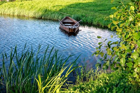 A small wooden rowing boat with a broken bottom on a calm lake near the shore. Belarus