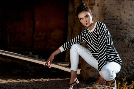 Beauty Fashion Model Girl with Brown Hair on a background of an old, abandoned building, wearing stylish clothes. Sexy woman portrait with perfect make-up and fashionable clothes. Beauty Trends