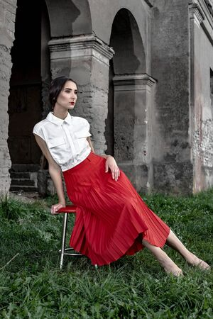 Beauty Fashion Model Girl with brown hair against the background of an old, abandoned building, in a stylish red skirt and shirt. Sexy woman portrait with perfect make up and fashion clothes. Beauty T