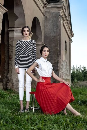 Outdoor fashion portrait of two young beautiful women wearing fashionable clothes posing on the street against the background of an old abandoned building.