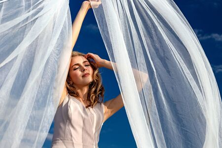 Portrait of a blonde girl in a dress against the background of the blue sky and white transparent fabric that the wind blows. On a sunny day 写真素材