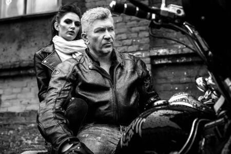 A brunette girl sits with a gray-haired man in leather jackets on a motorbike on a background of a brick old wall. Black and white photography Standard-Bild - 137740672