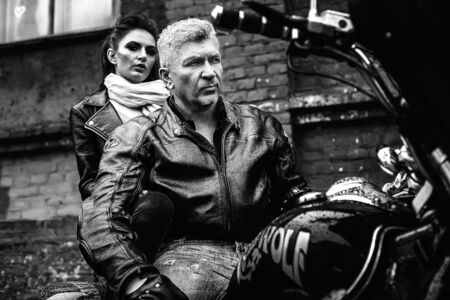 A brunette girl sits with a gray-haired man in leather jackets on a motorbike on a background of a brick old wall. Black and white photography Standard-Bild - 137740679