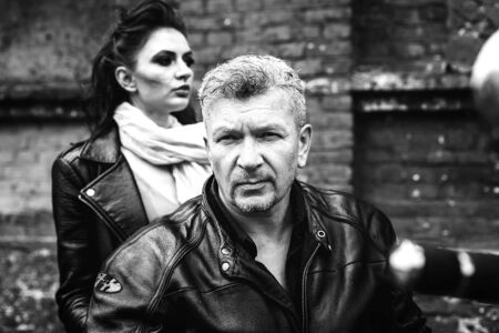 A brunette girl sits with a gray-haired man in leather jackets on a motorbike on a background of a brick old wall. Black and white photography Standard-Bild - 137740690