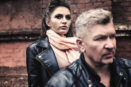 A brunette girl sits with a gray-haired man in leather jackets on a motorbike on a background of a brick old wall. Standard-Bild - 137740707