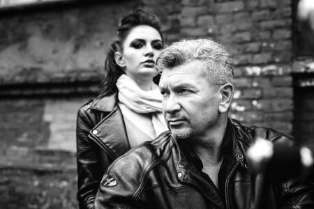 A brunette girl sits with a gray-haired man in leather jackets on a motorbike on a background of a brick old wall. Black and white photography Standard-Bild - 137740710