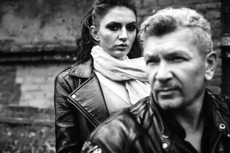 A brunette girl sits with a gray-haired man in leather jackets on a motorbike on a background of a brick old wall. Black and white photography Standard-Bild - 137740713
