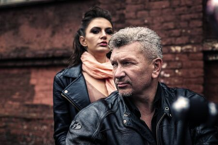 A brunette girl sits with a gray-haired man in leather jackets on a motorbike on a background of a brick old wall. Standard-Bild - 137740748