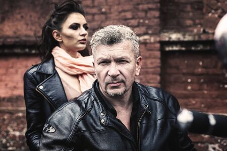A brunette girl sits with a gray-haired man in leather jackets on a motorbike on a background of a brick old wall. Standard-Bild - 137740749