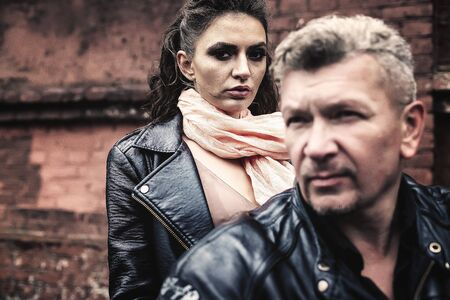 A brunette girl sits with a gray-haired man in leather jackets on a motorbike on a background of a brick old wall. Standard-Bild - 137740757