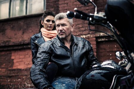 A brunette girl sits with a gray-haired man in leather jackets on a motorbike on a background of a brick old wall. Standard-Bild - 137740760