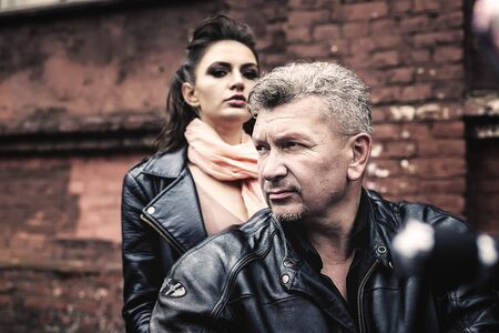 A brunette girl sits with a gray-haired man in leather jackets on a motorbike on a background of a brick old wall. Standard-Bild - 137740769