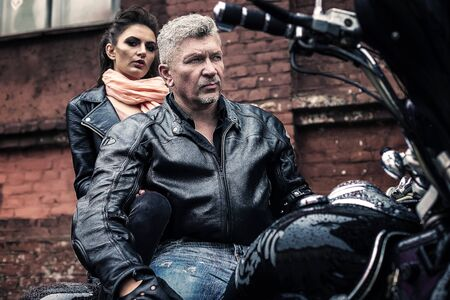A brunette girl sits with a gray-haired man in leather jackets on a motorbike on a background of a brick old wall. Standard-Bild - 137740777