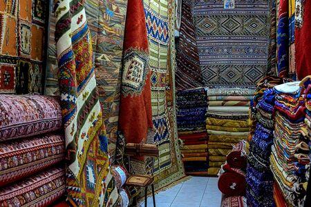 Marokkanische Teppiche mit leuchtenden Farben zum Verkauf in der engen Straße von Rabat in Marokko mit selektivem Fokus. Marokko