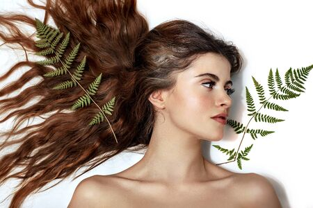 Portrait of an adult brunette woman on a white background with green fern, skin care concept, beautiful skin and hands with nail manicure. Фото со стока