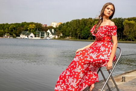 Portrait of a beautiful young brown-haired girl with long hair in a red dress on a lake background. Belarus