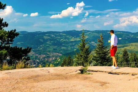 A young guy looks down at the valley and the mountains standing on a high point. Bosnia and Herzegovina, Sarajevo, August 2018