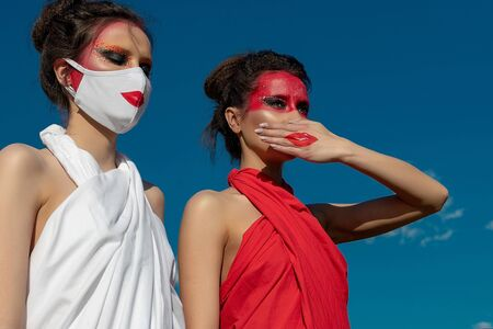 Two beautiful young brunette girls with creative bright makeup in tunics against a blue sky. One girl in a mask, the other girl closes her mouth with her hand. 免版税图像