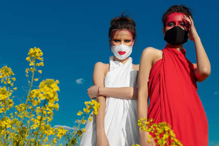 Two beautiful young brunette girls with creative bright makeup in tunics on a background of a field of yellow flowers and blue sky. One girl in a mask, the other girl closes her mouth with her hand.