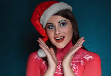 A young brunette woman with ideal art make-up and wearing a Santa Claus cap is surprised, admires