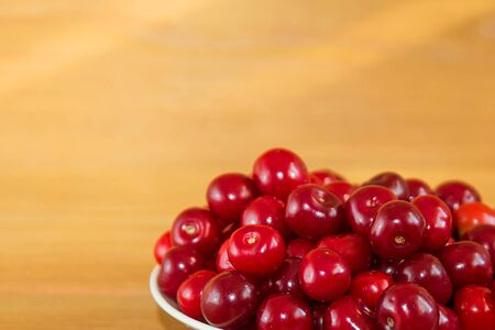 Ripe red cherries on a wooden background. Red berries on a plate on a brown background. 写真素材