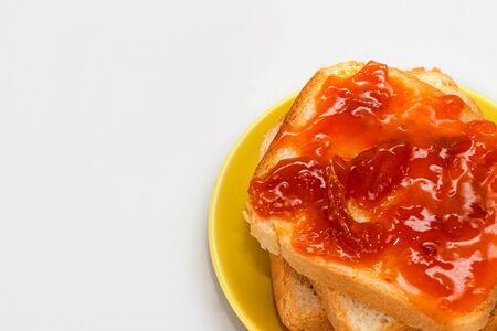 Bread and apricot jam on a white background. toast with jam. Dessert for breakfast. Slices of bread with jam. High-calorie sandwiches.