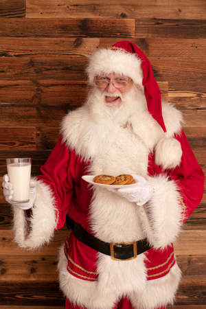 Funny real Santa Claus with glass of milk and delicious cookies.