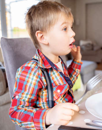 Hungry little kid waiting for the dinner at home, holding fork in hand.